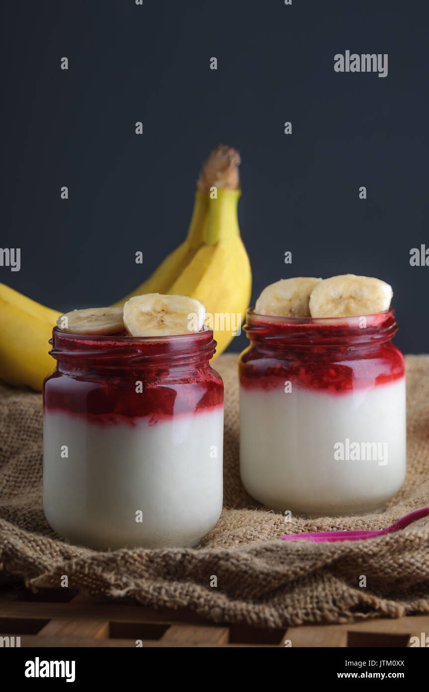 Yoghurt topped with berry and banana on burlap fabric. Black background. - Stock Image