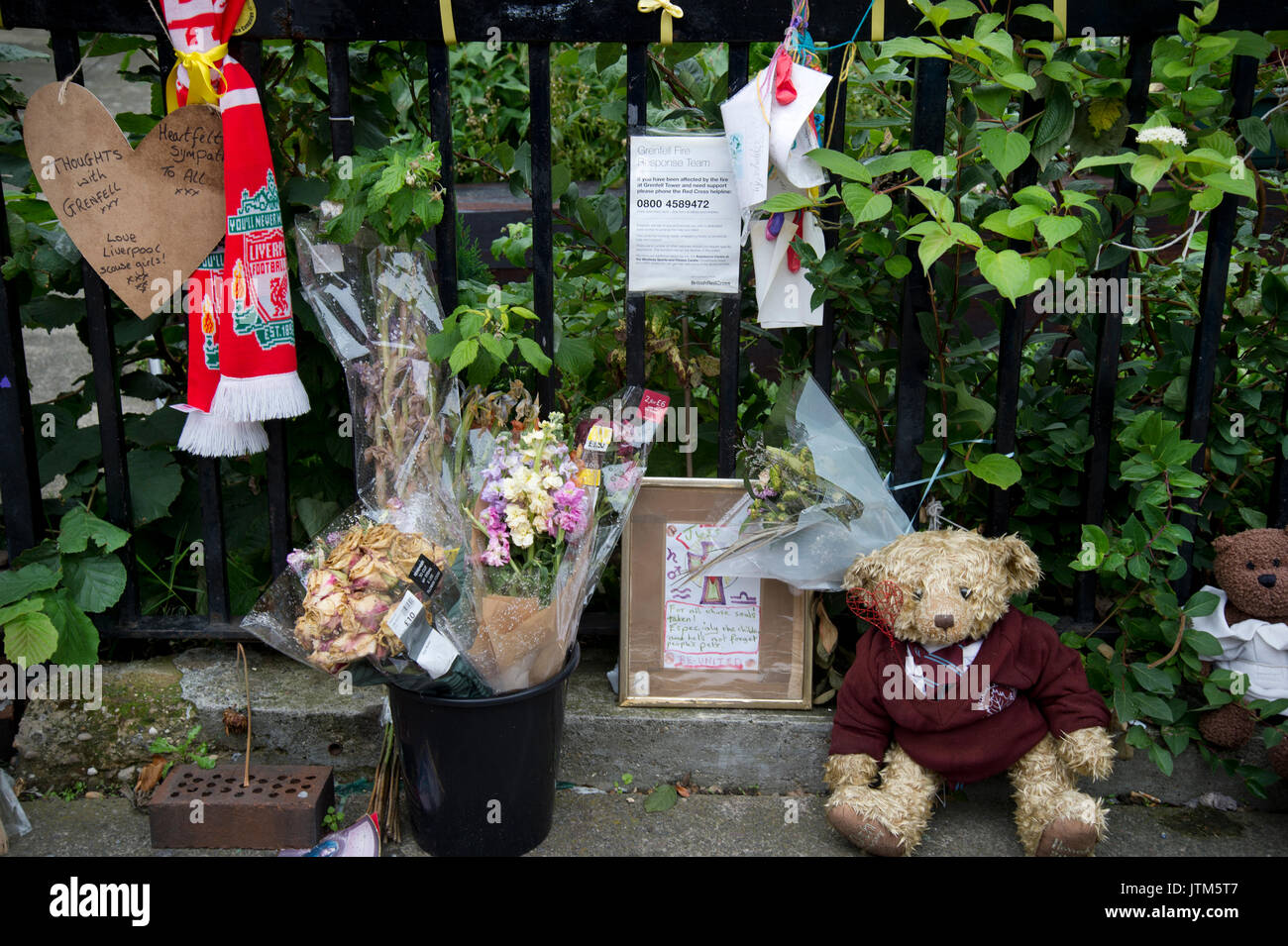 Grenfell Tower,Kensington, West London. Aftermath of the tragedy. memorial to victims of the fire.Flowers, teddy bear and football scarf. - Stock Image