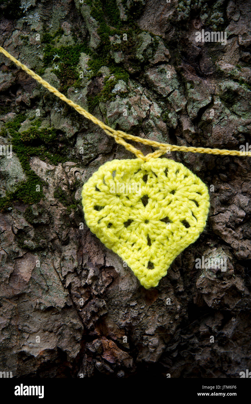Grenfell Tower, West London. Aftermath of the tragedy. Yellow crocheted heart to honour the missing tied around a tree near the burnt-out tower - Stock Image