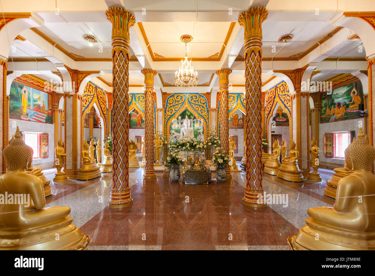 Gilded standing, seated and reclining Buddha statues inside the Viharn hall at Wat Chalong Temple in Phuket, Thailand Stock Photo