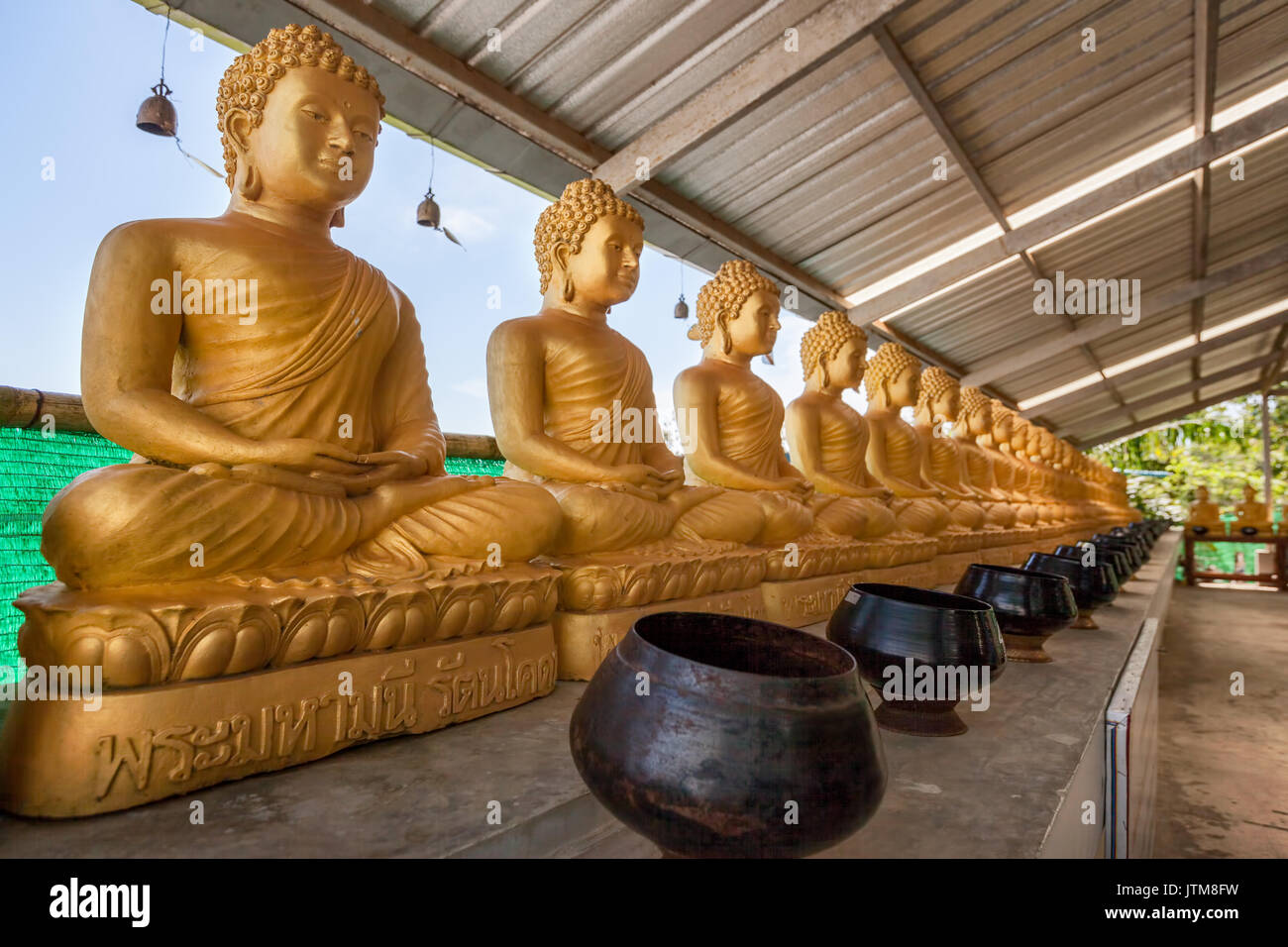 Buddha statues with bronze bowls for donations at the Phuket Big Buddha Park, Chalong, Thailand - Stock Image