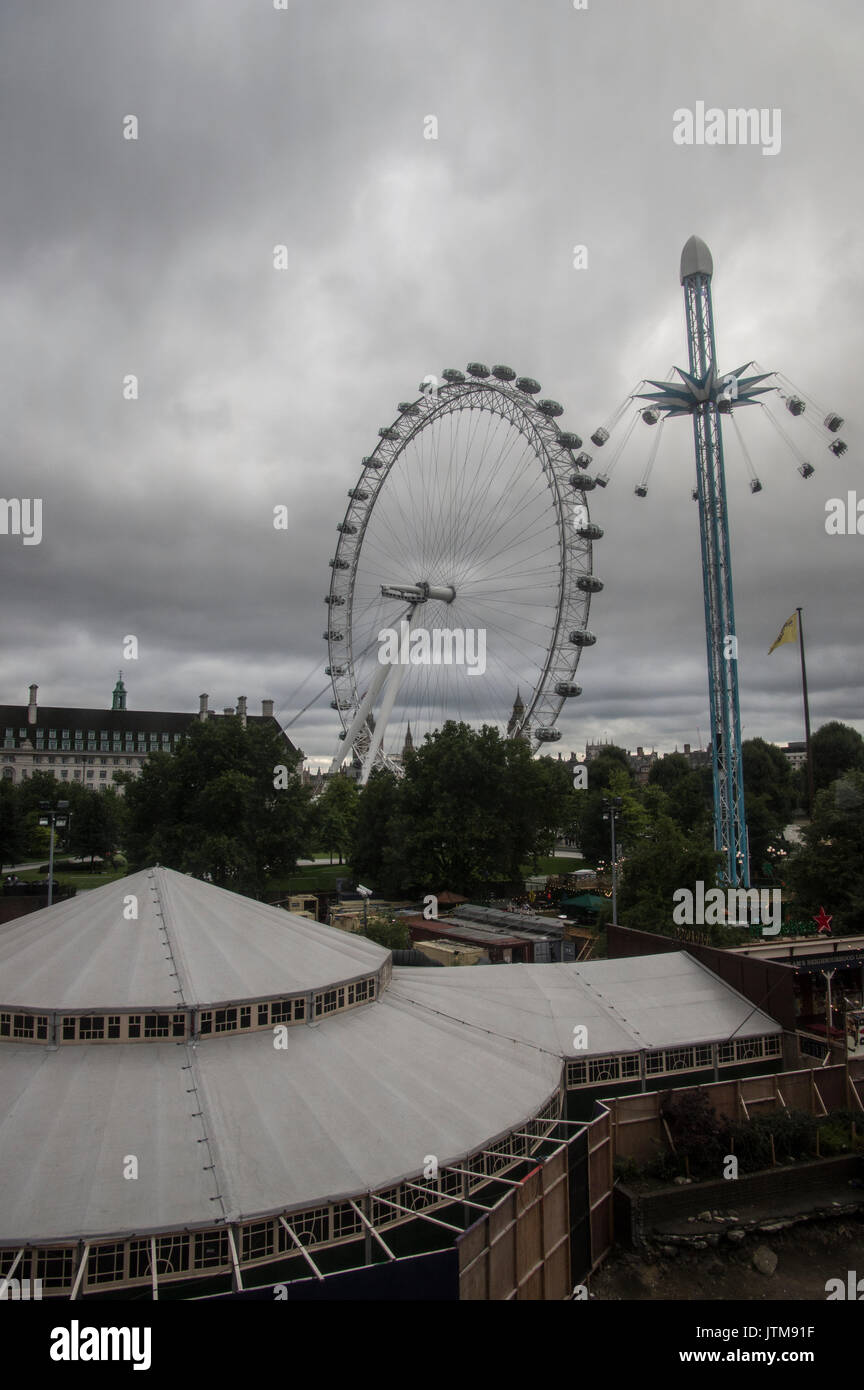 Overcast, cloudy day in London with a view of an amusement park ride and the London Eye ferris wheel against the Stock Photo