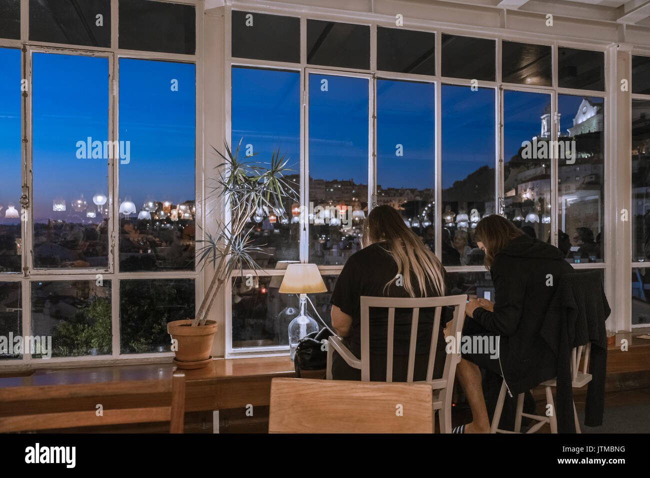 Two young women in a cafe absorbed with their smartphones sitting opposite a panoramic view of Lisbon city centre at twilight, Portugal. - Stock Image