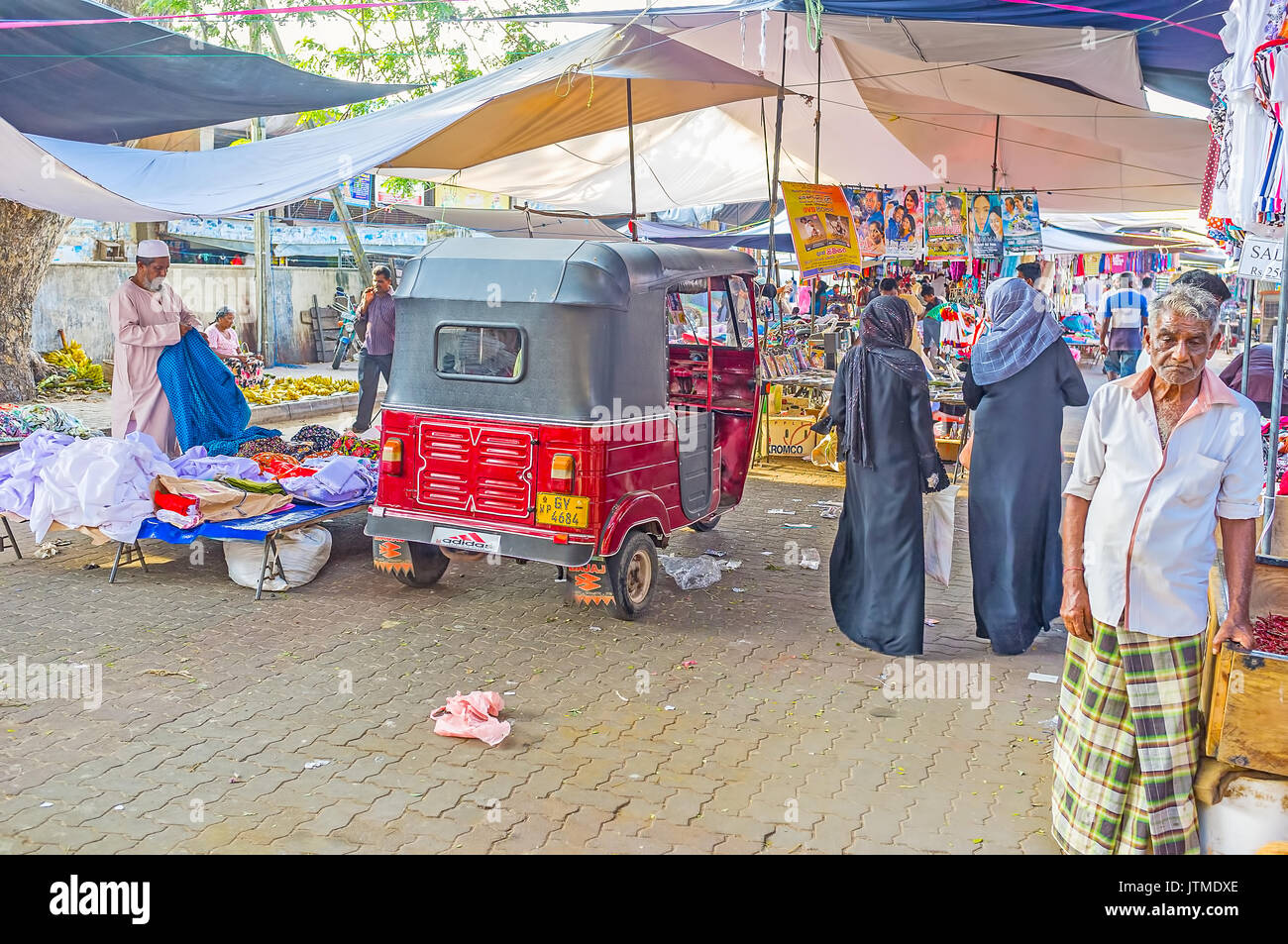 NEGOMBO, SRI LANKA - DECEMBER 7, 2016: The old clothes market in residential district of the city, tuk-tuk is parked Stock Photo