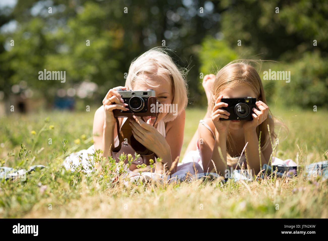 Mom and daughter taking pictures lying on blanket in park. - Stock Image