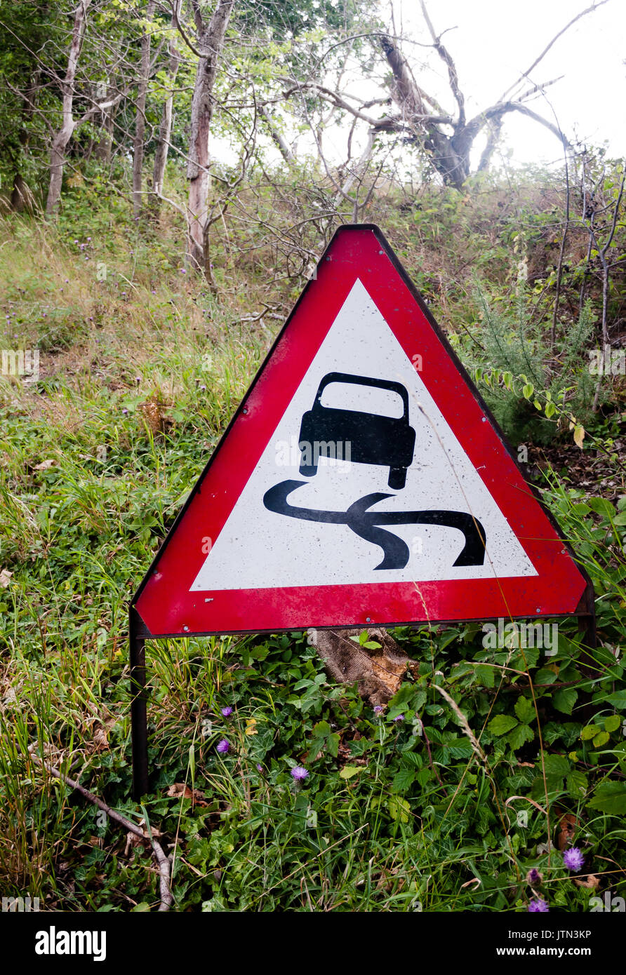 a red triangle driving sign on the side of road on grass; UK - Stock Image