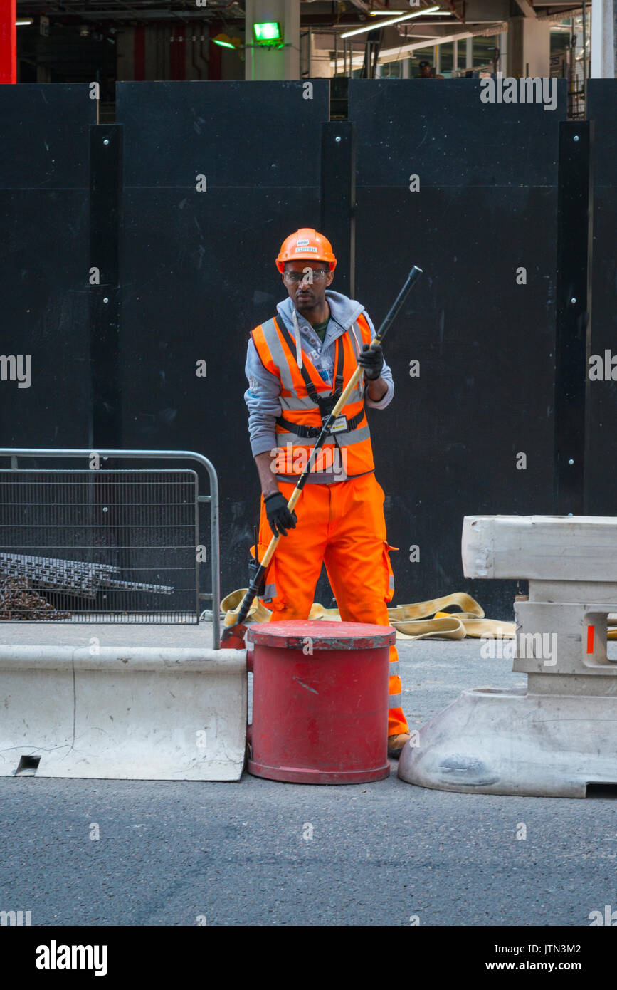 UK London City Lime Street British workman high vis jacket trousers safety helmet glasses standing looking pole in hand - Stock Image