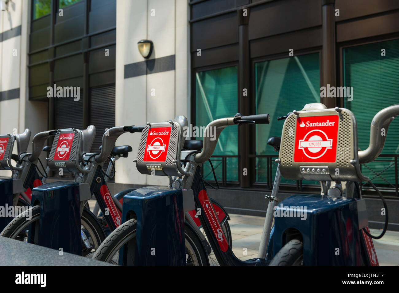 UK London City Aldgate St Mary Axe Santander bikes cycles bicycles hire rental park station detail signage logo red livery marketing Transport for TFL - Stock Image
