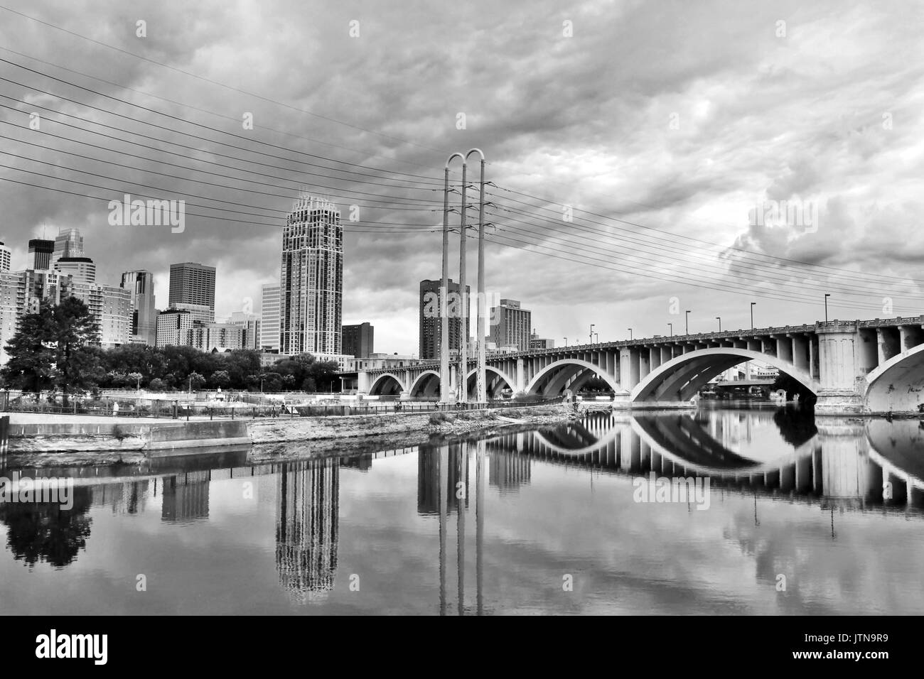 Minneapolis downtown skyline and Third Avenue Bridge above Mississippi river in black and white. Midwest USA, state of  Minnesota. - Stock Image