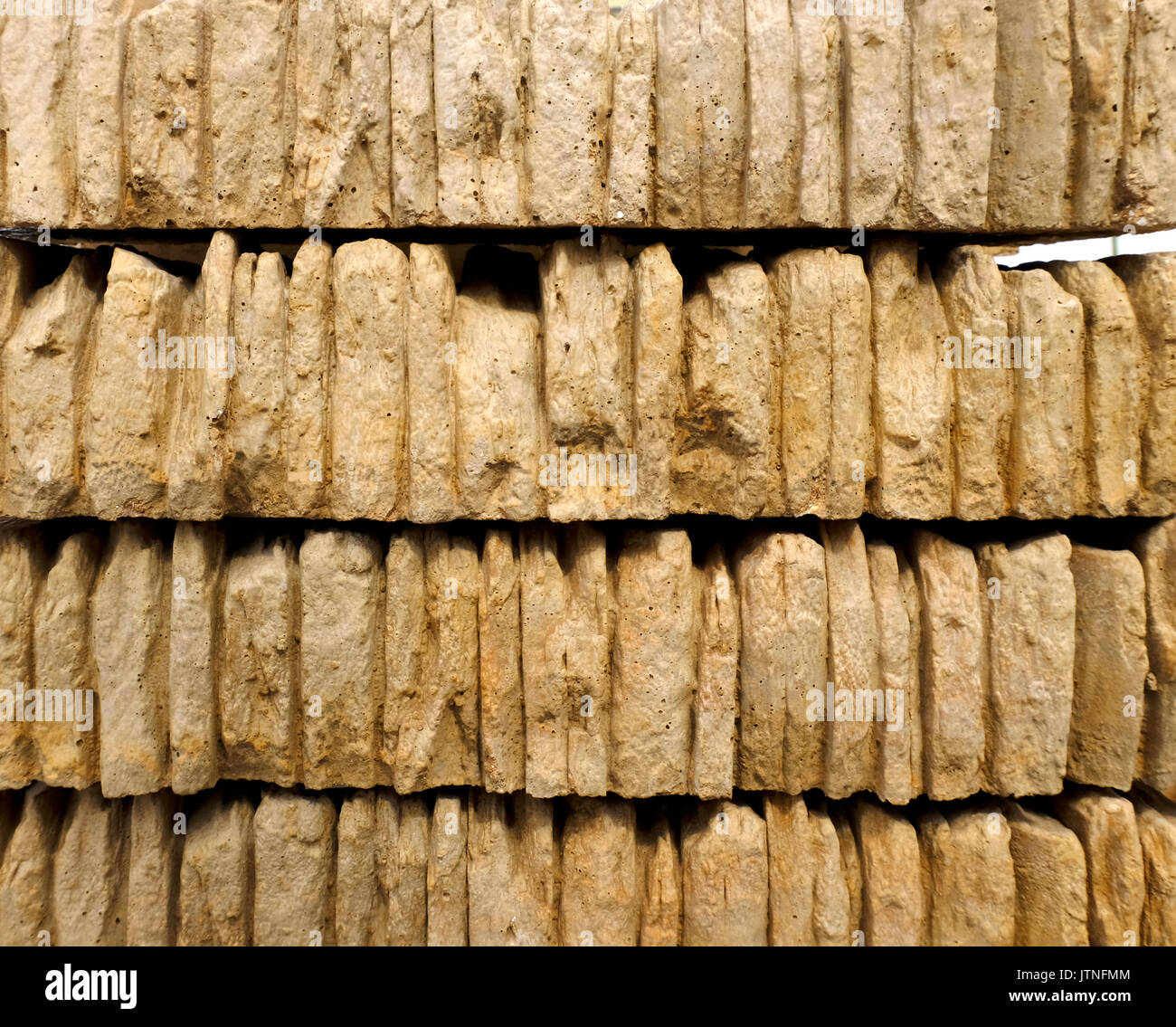 Stacks of gold coloured walling or coping stone for finishing off the top of a wall - Stock Image