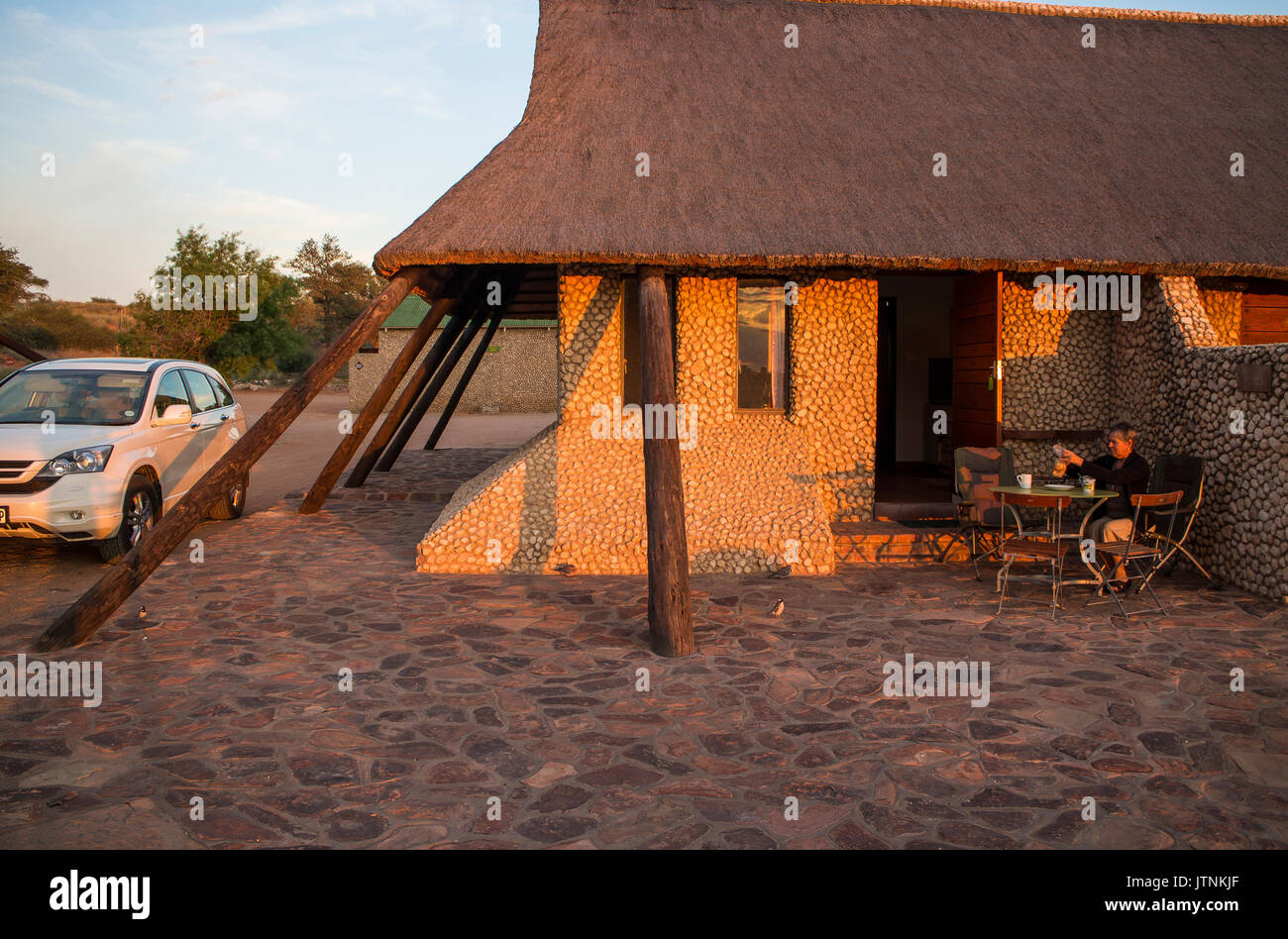 Tourists enjoy an early morning coffee in Tweerivieren camp before heading out on a game viewing drive in the Kgalagadi Transfrontier Park - Stock Image