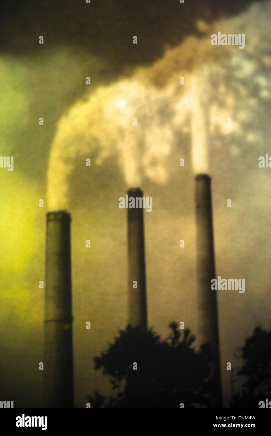 Industrial smoke stacks emitting smoke. - Stock Image
