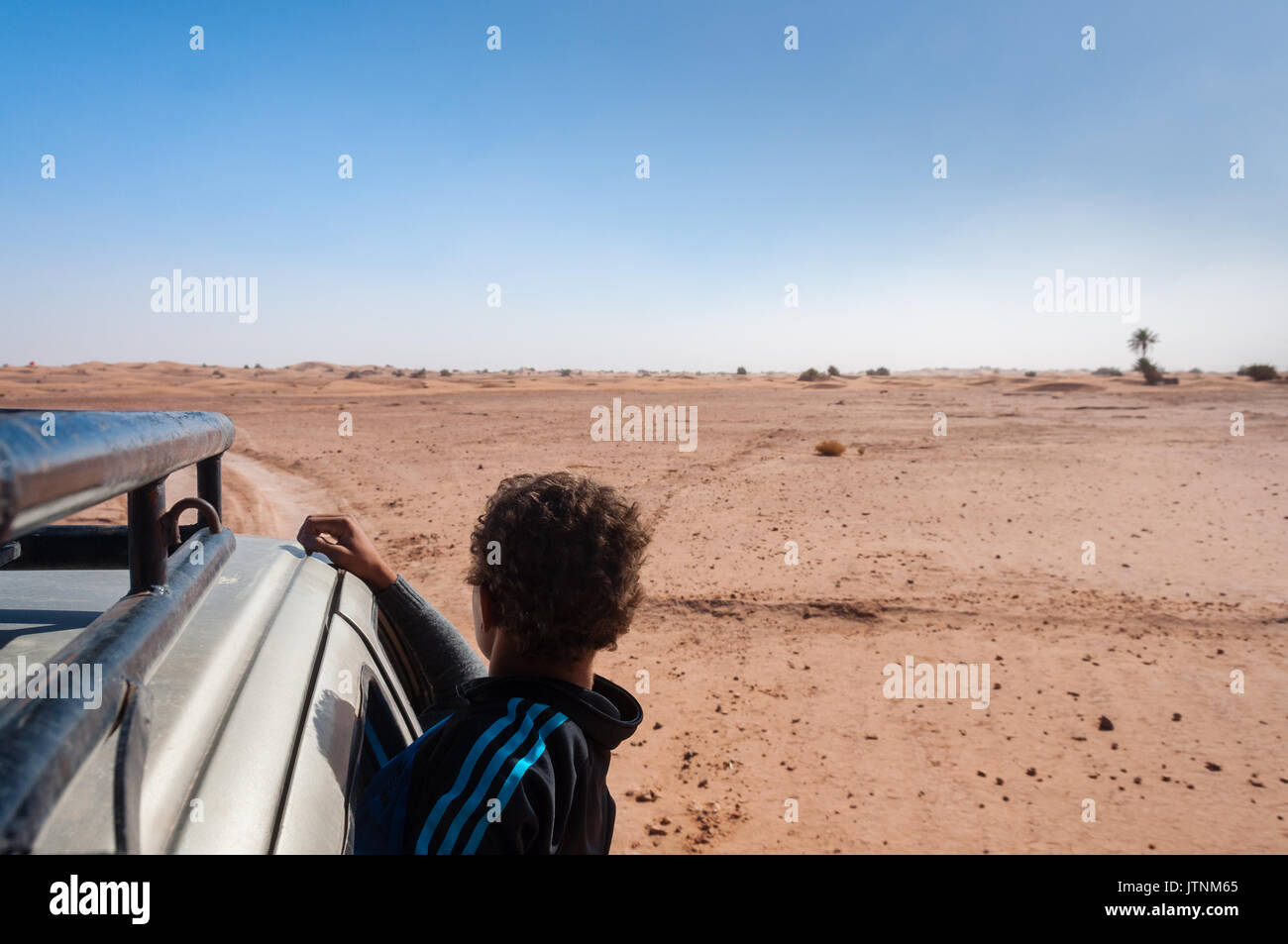 Child hanging outside a car, Desert - Stock Image