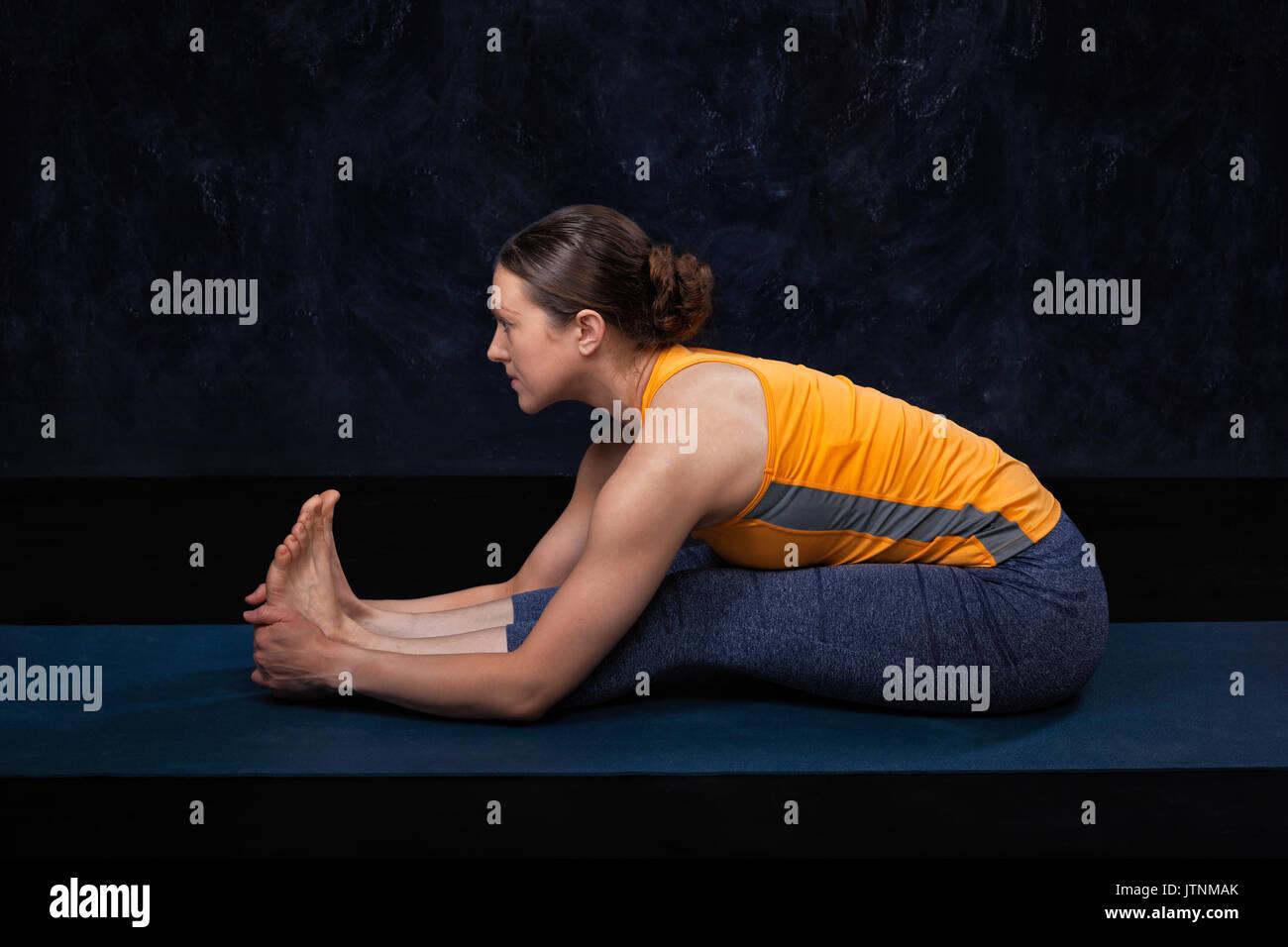 Woman doing Hatha yoga Ashtanga Vinyasa yoga asana Paschimottana - Stock Image