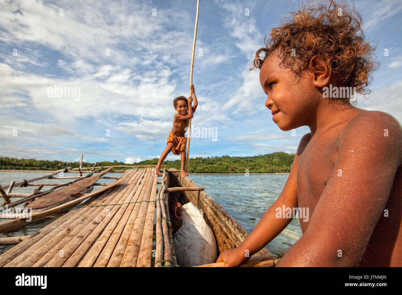 Children playing with a outrigger canoe in the village of Hessessai Bay at PanaTinai (Panatinane)island in the Louisiade Archipelago in Milne Bay Province, Papua New Guinea. The island has an area of 78 km2. The Louisiade Archipelago is a string of ten larger volcanic islands frequently fringed by coral reefs, and 90 smaller coral islands located 200 km southeast of New Guinea, stretching over more than 160 km and spread over an ocean area of 26,000 km? between the Solomon Sea to the north and the Coral Sea to the south. The aggregate land area of the islands is - Stock Image