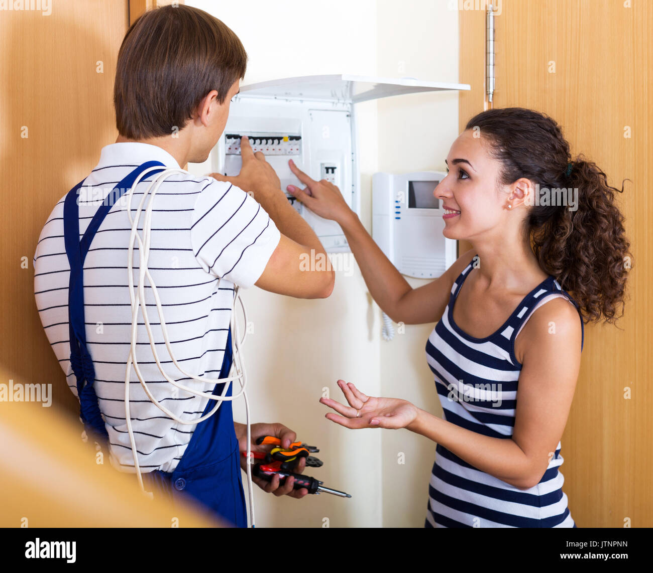 Smiling female client needs professional help of electrician at home ...