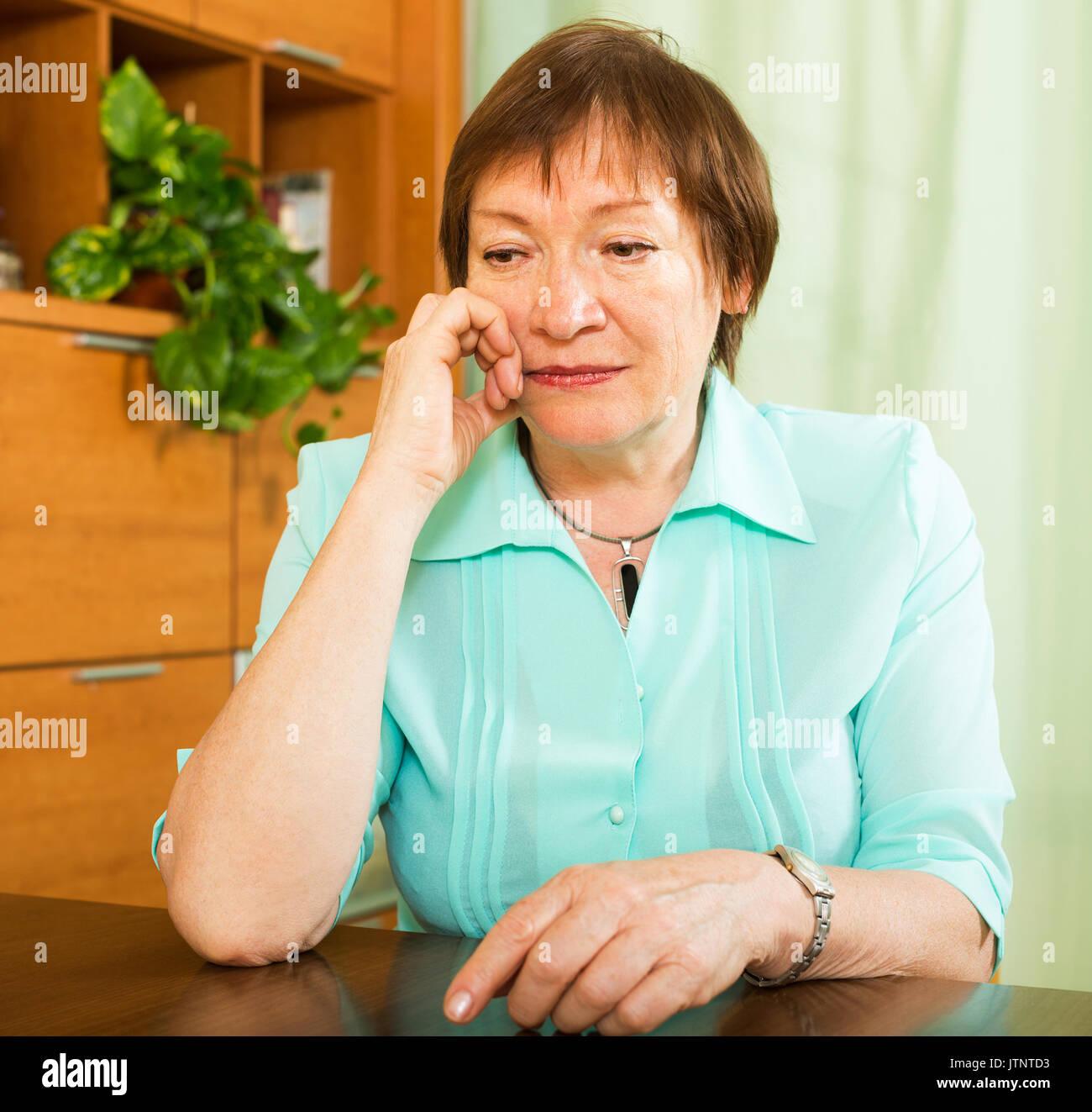 Portrait of sad senior woman having tough time   at home - Stock Image