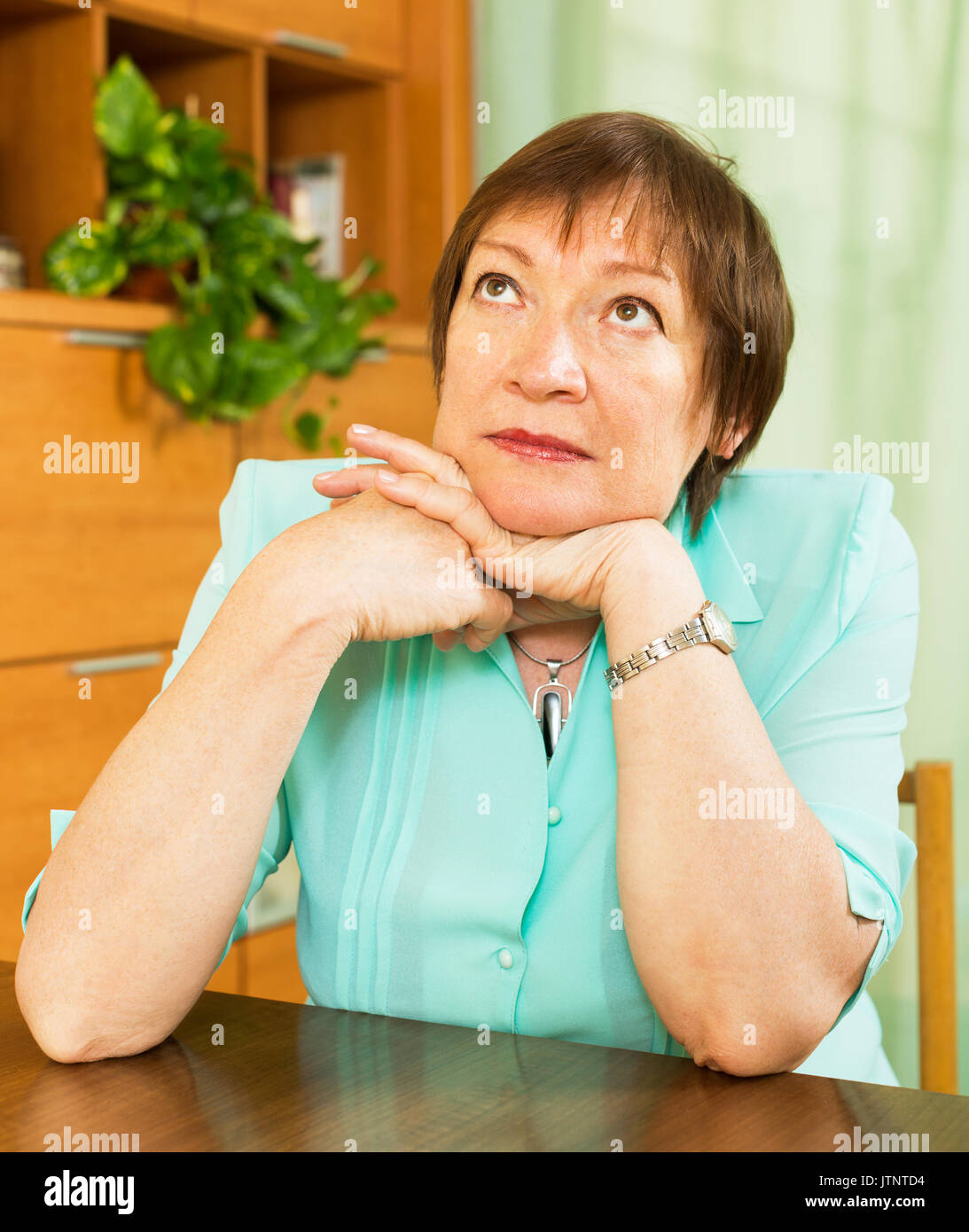 Female pensioner  with sad face  in  home interior - Stock Image