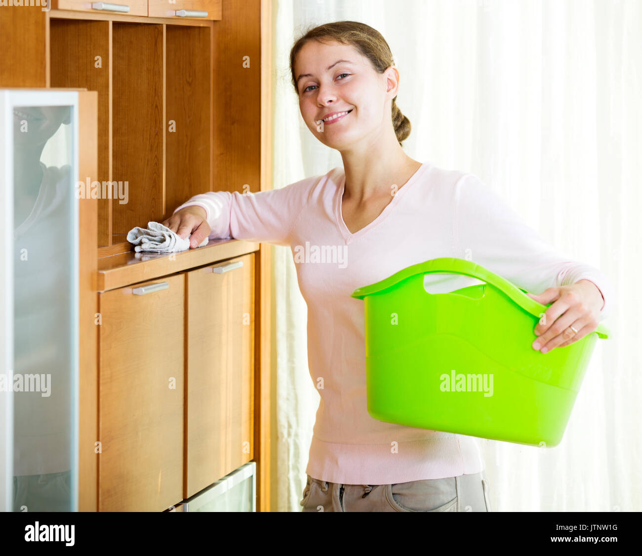 dusting furniture. Portrait Adult Woman Dusting Furniture At Home And Smiling - Stock Image F