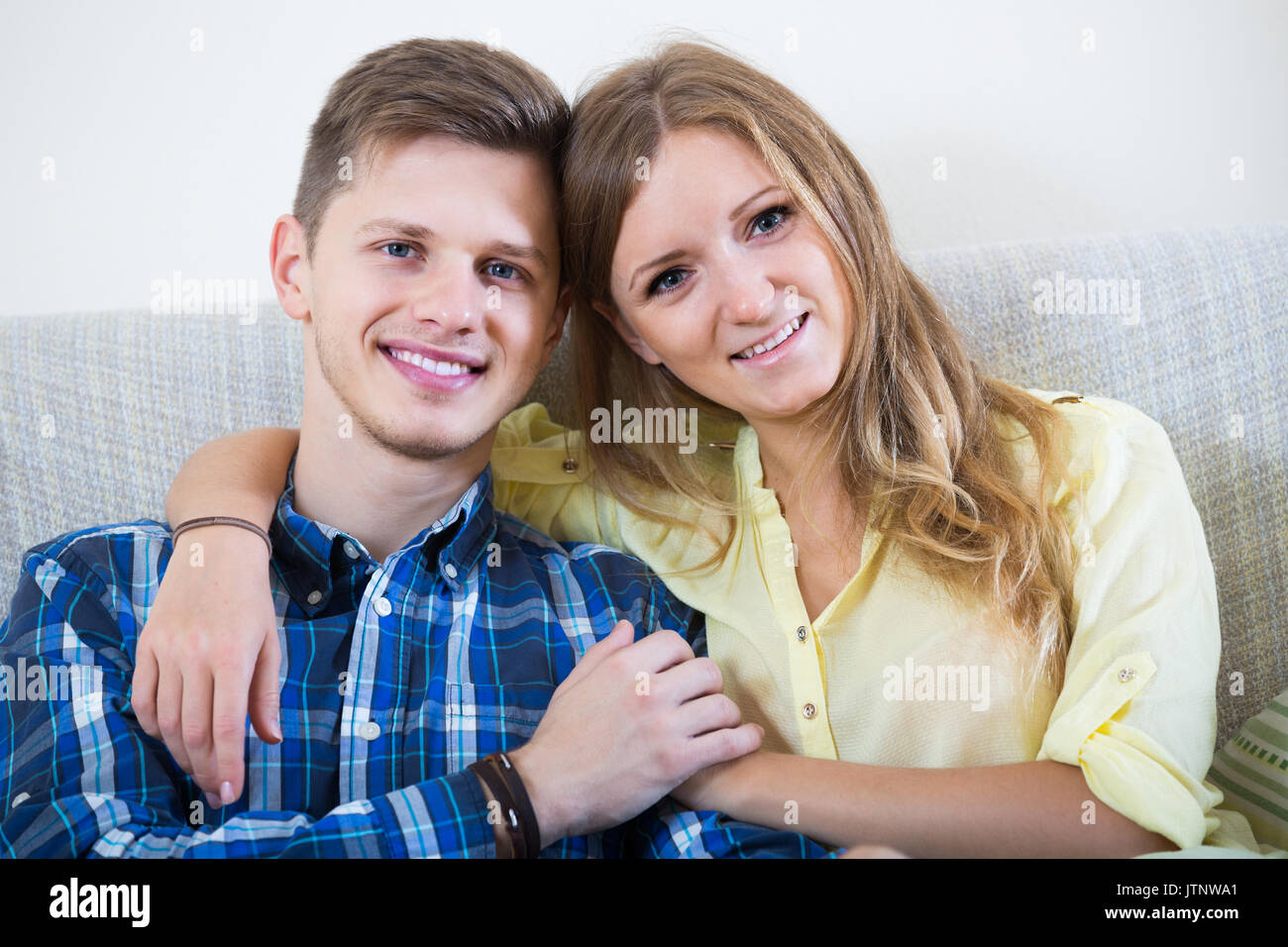 1290c98b8655 young european guy and pretty girl cuddling on sofa indoors Stock ...