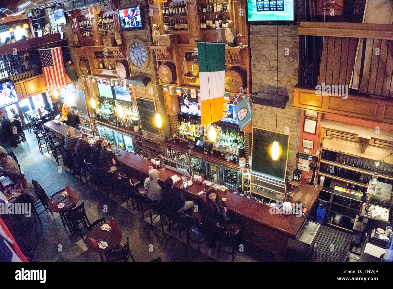 spacious old Irish pub on W 36th street, decor unchanged as Garment district gentrified to admit offices & residential towers among low manufacturing - Stock Image