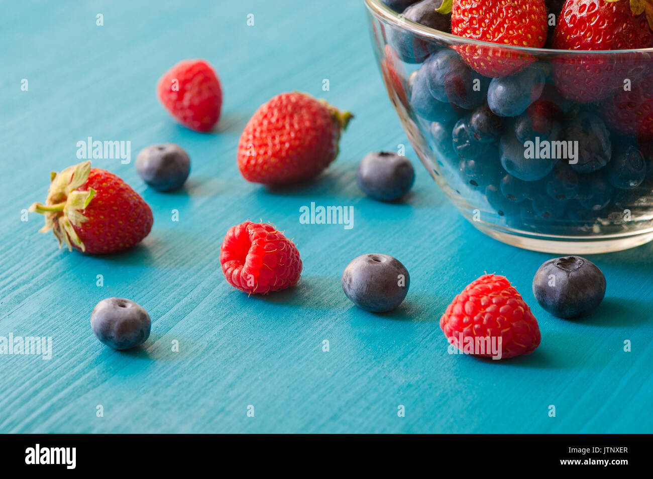 Blueberries and strawberry in Glass bowl on wooden table background - Stock Image