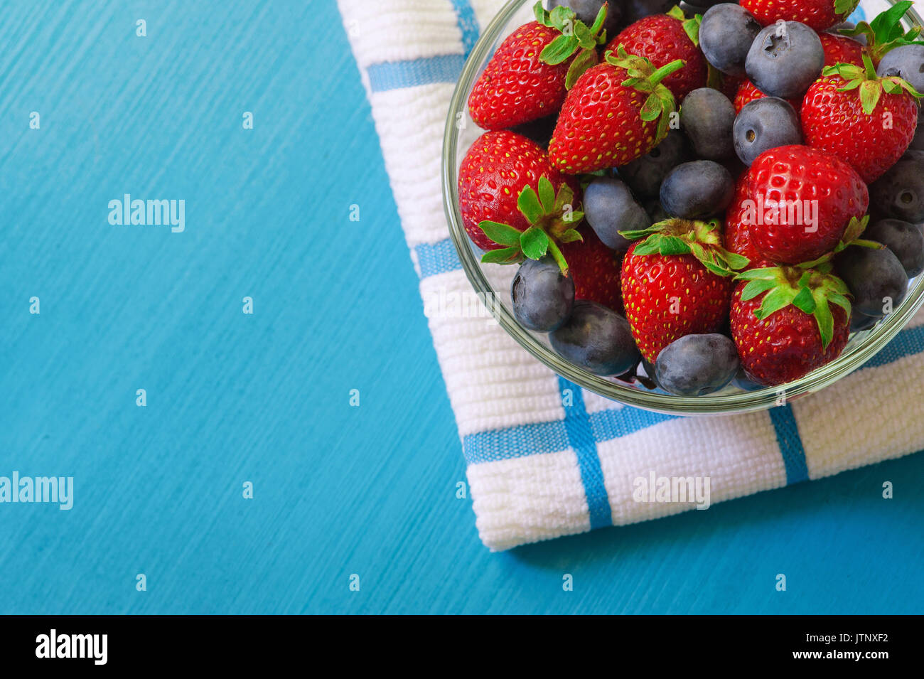 Glass bowl with assortment berries blueberries, strawberries and blackberries at white textile napkin over blue wooden table. Natural day light. Top v - Stock Image
