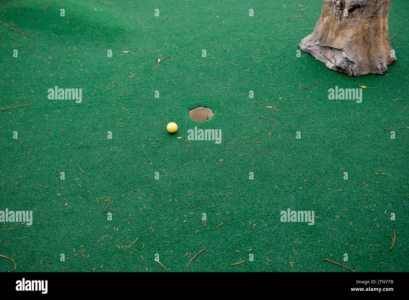 golf ball near hole - Stock Image