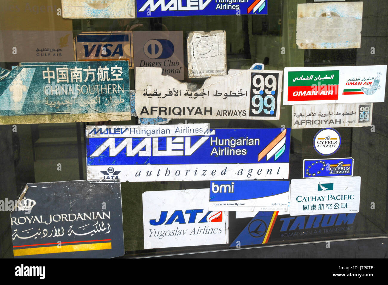 Airline logos including historic now non existing Yugoslav Airlines (JAT) through the window of travel agency in downtown Cairo - Stock Image