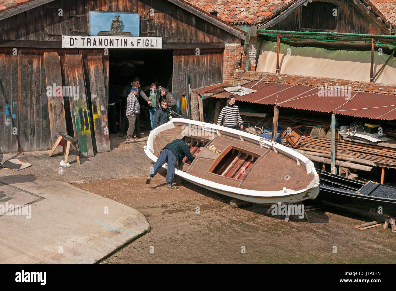 Men working on the boat building of Gondolas in a canal