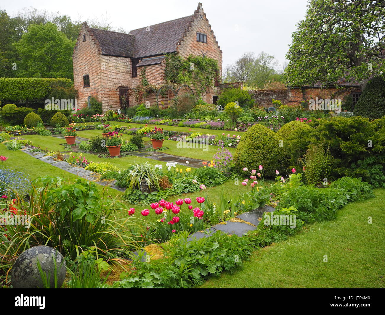 Chenies Manor sunken garden. Wet afternoon at tulip time; ornamental pond, apple tree, fresh greenery and plant Stock Photo