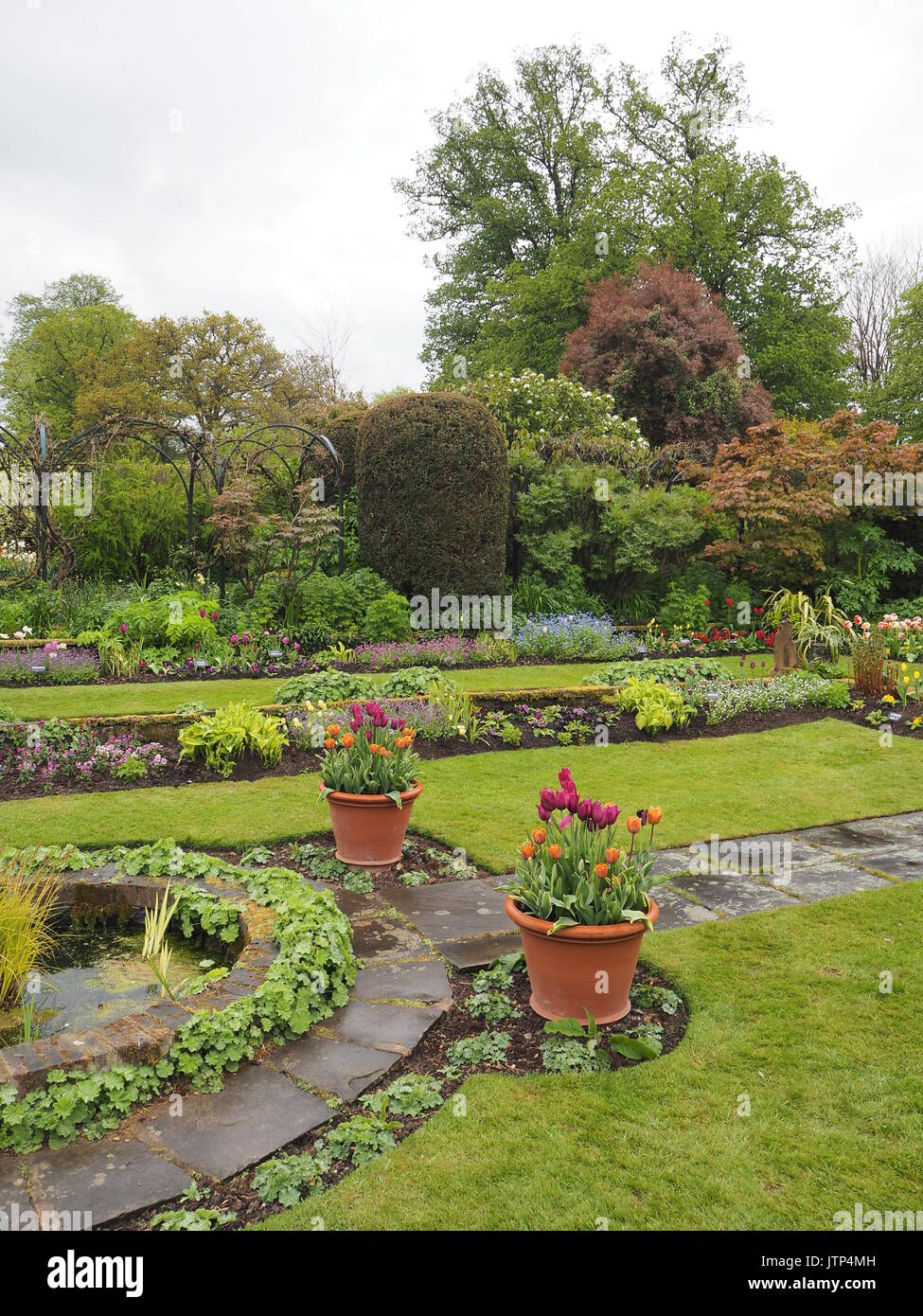 Portrait view of Chenies Manor sunken garden looking south west in springtime with tulips, ornamental pond, archways, Stock Photo