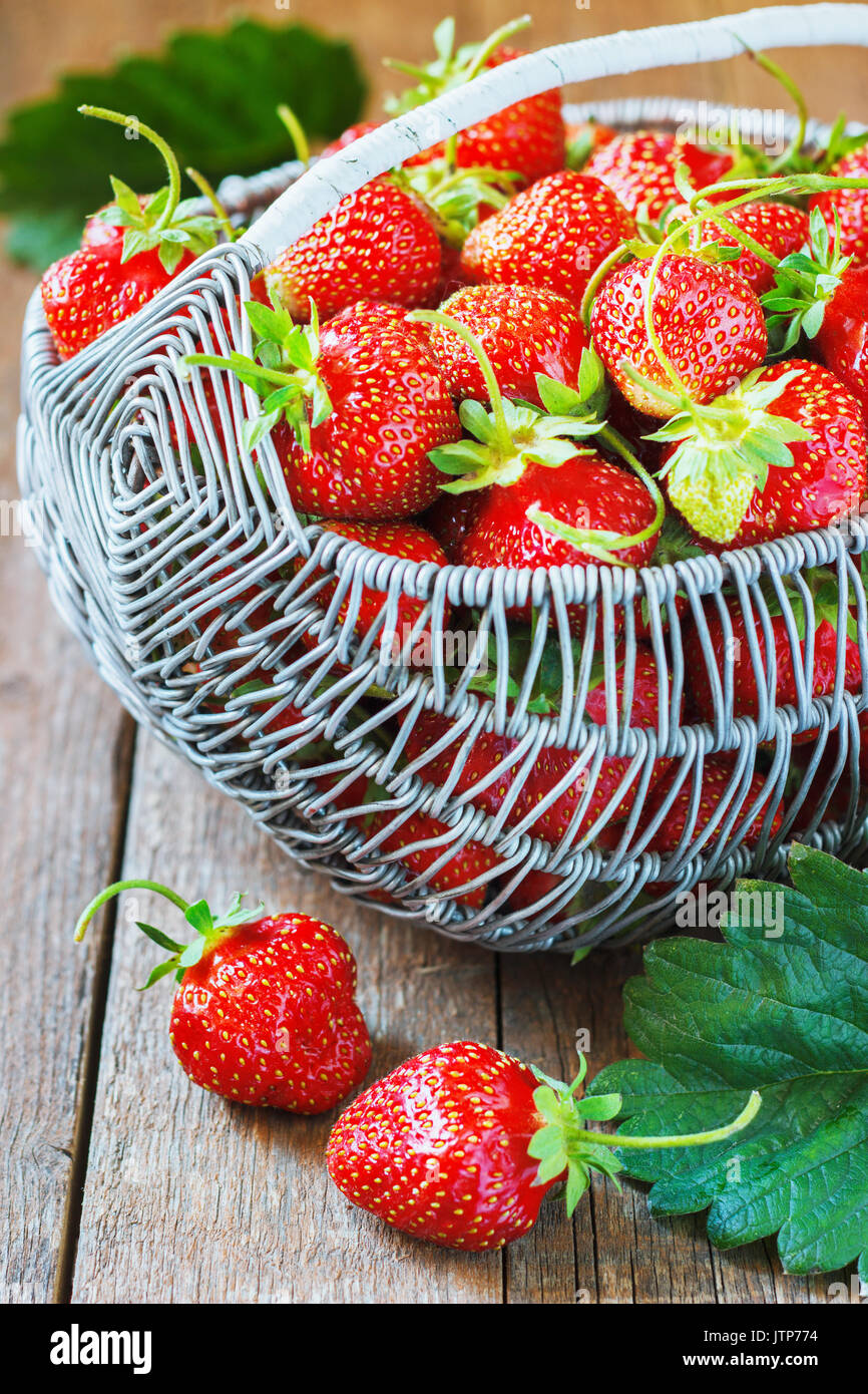 Juicy fresh strawberries in a basket on wooden background, selective focus. - Stock Image