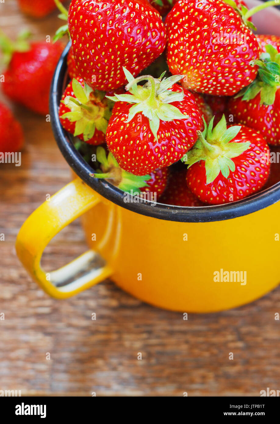 Strawberry Garden Rustic Cup Summer Food yellow Metal dark Background Selective Focus - Stock Image