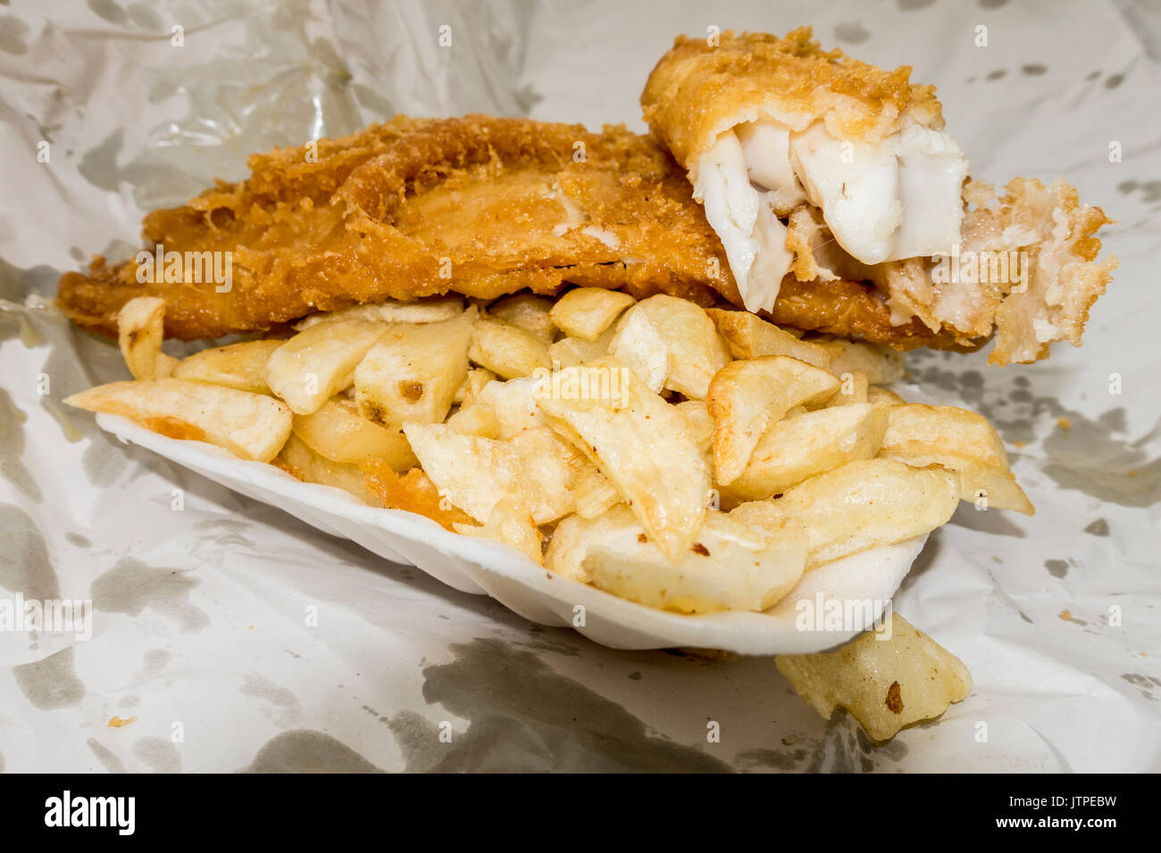 Traditional British fast food takeaway meal of battered fish and chips, in the container and paper wrapping. Stock Photo