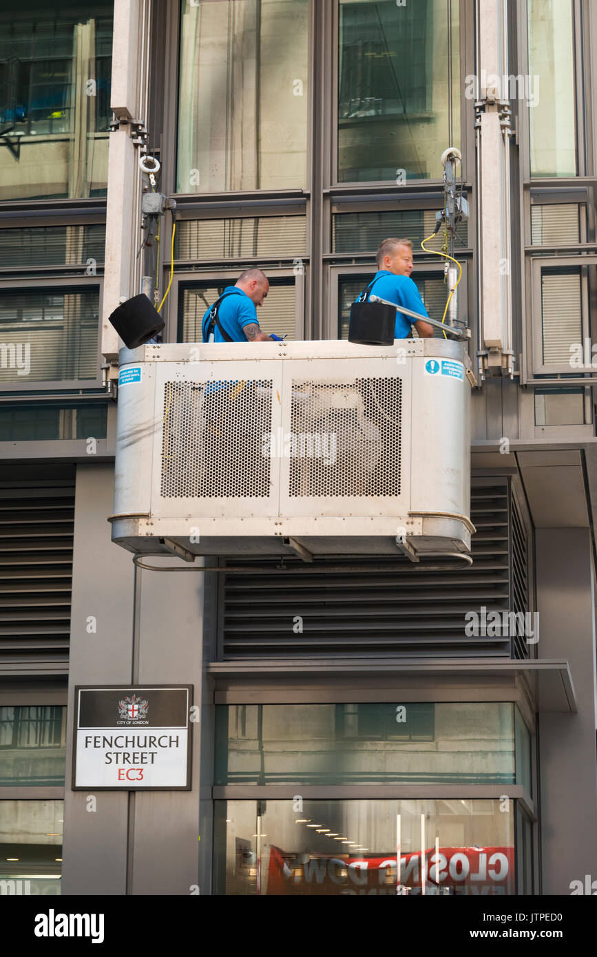 UK London City Financial Centre Center Fenchurch Street British workmen suspended hanging cradle texting cell mobile phone watching passers by - Stock Image