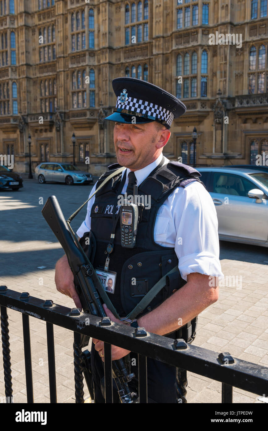 UK London Westminster Palace of Westminster Houses of Parliament Old Palace Yard armed policeman police officer cop smiling chatting to tourists - Stock Image