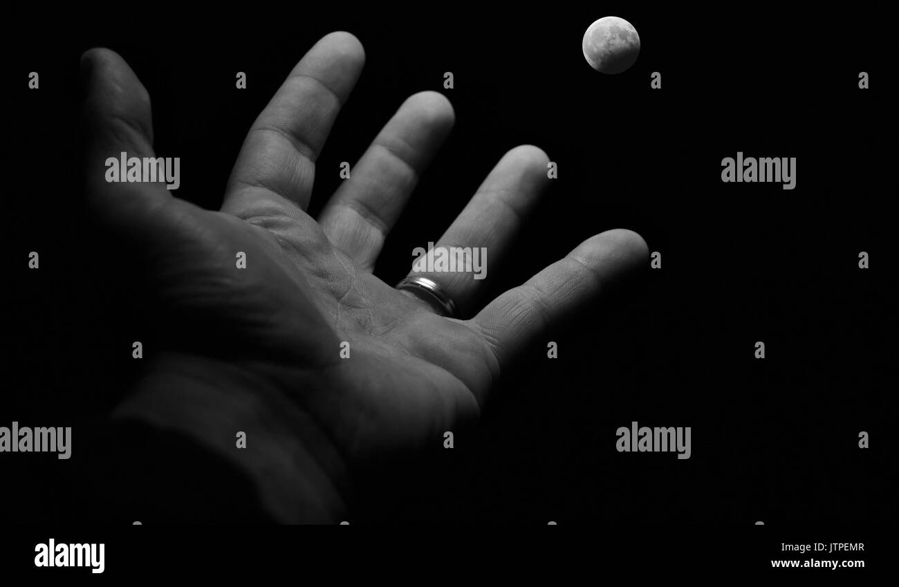 Black and white hand ,reaching out to the moon - Stock Image