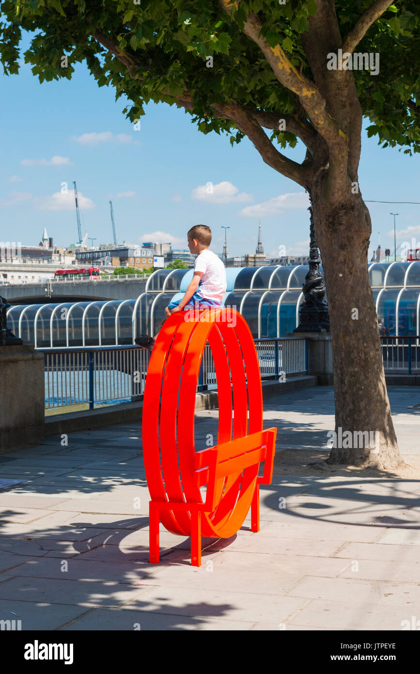 UK London Southbank embankment River Thames water futuristic red bench young boy child kid sitting perched top railings people Summer scene trees - Stock Image
