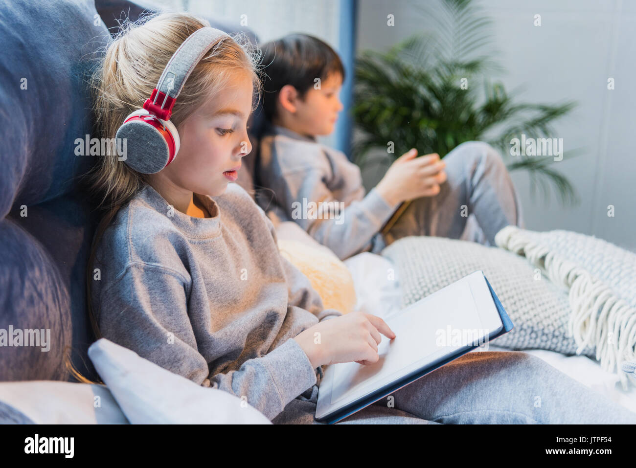 side view of focused girl in headphones and little boy using digital tablets - Stock Image