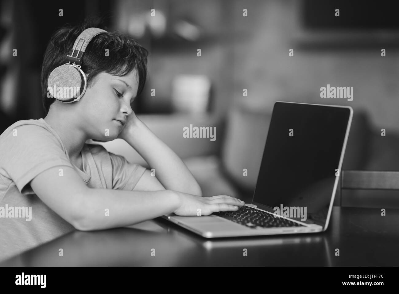 Kid boy listening music in headphones while sitting at home and typing on laptop black