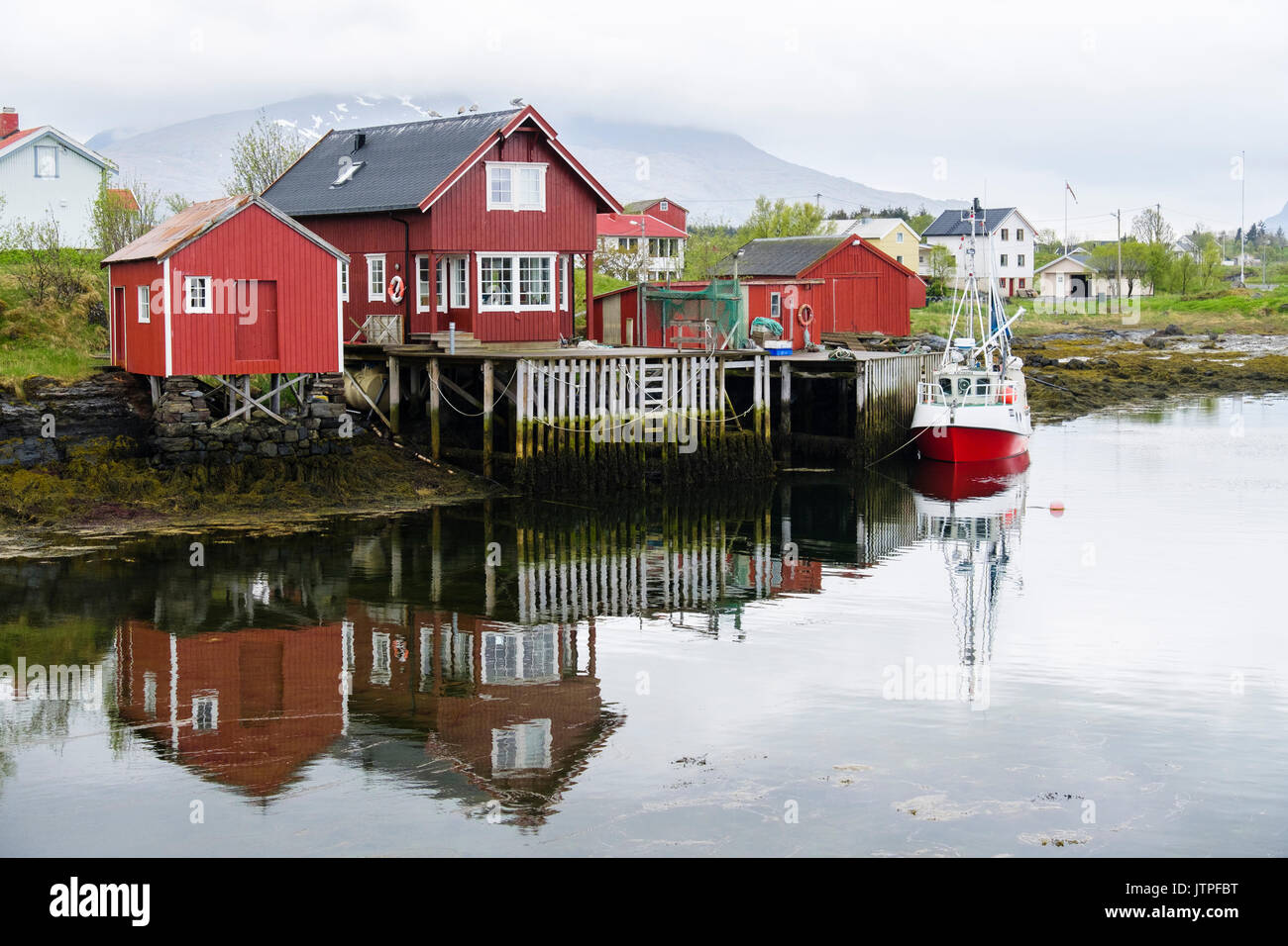 Fishing village with boats and wooden buildings on stilts. Nes, Vega Island, Norway, Scandinavia - Stock Image