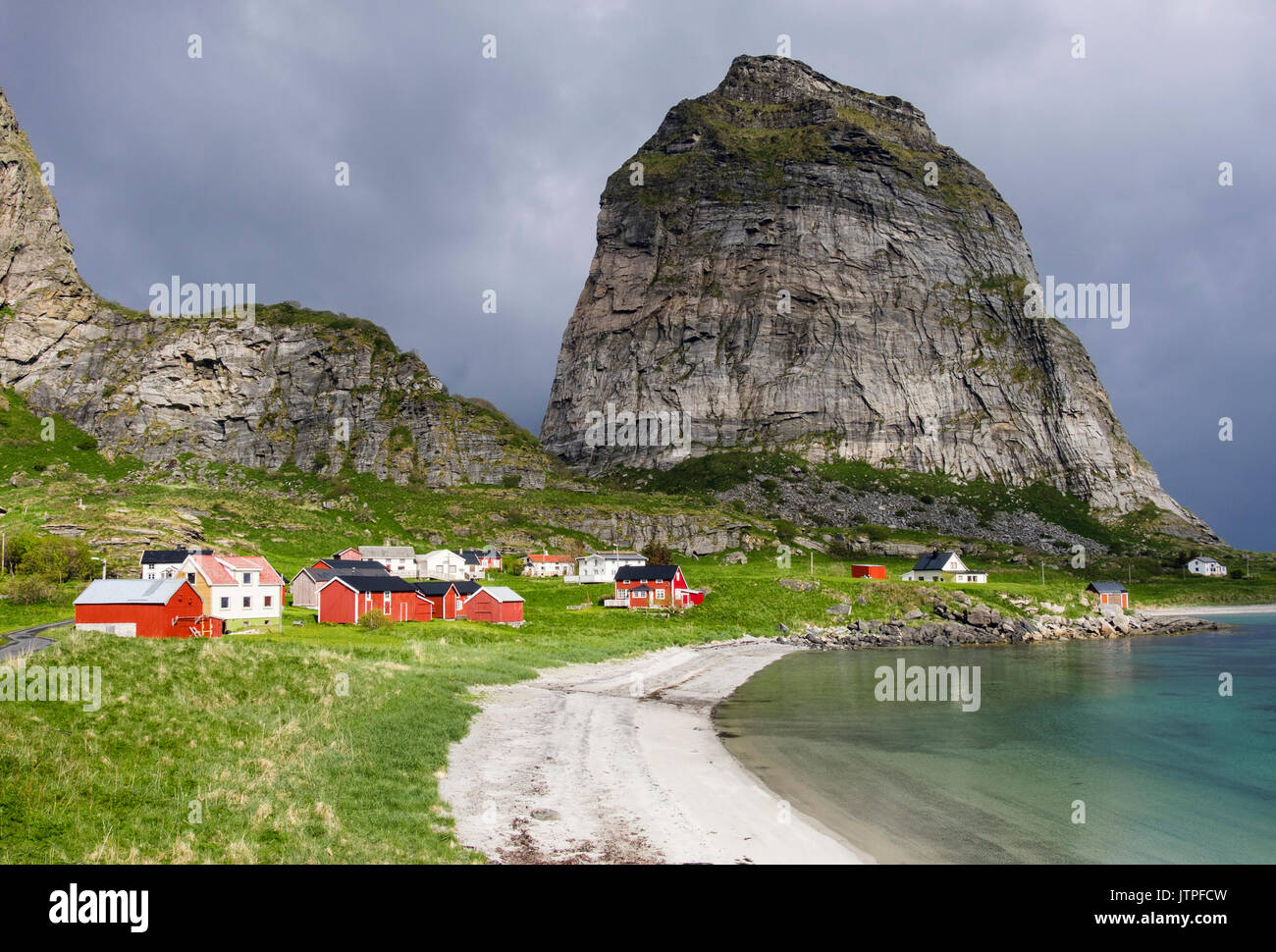 Old former fishing village houses around sandy beach below Trænstaven mountain on Sanna island, Træna, Nordland county, Norway, Scandinavia - Stock Image