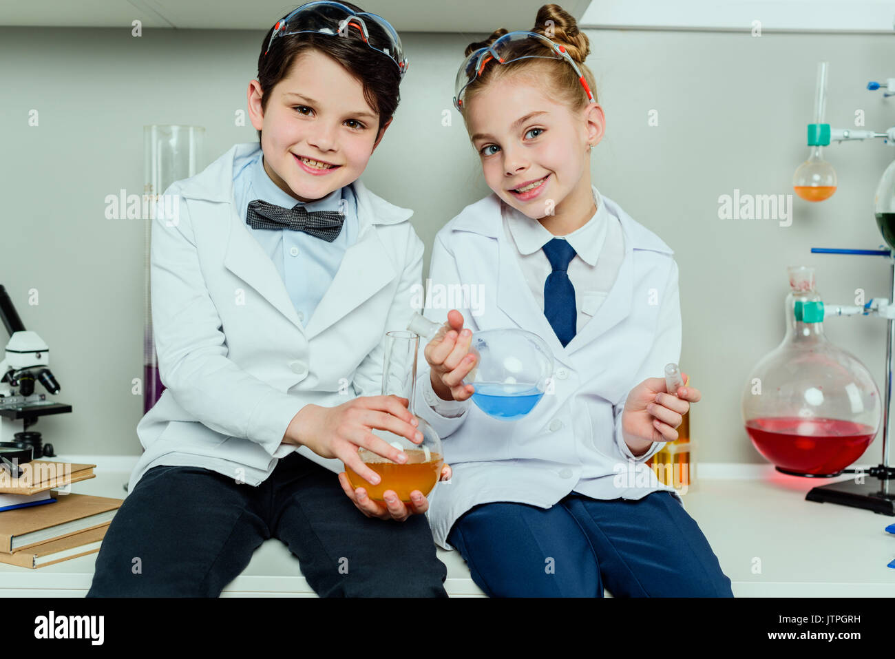 Schoolchildren in white coats holding reagents in flasks sitting in science laboratory - Stock Image