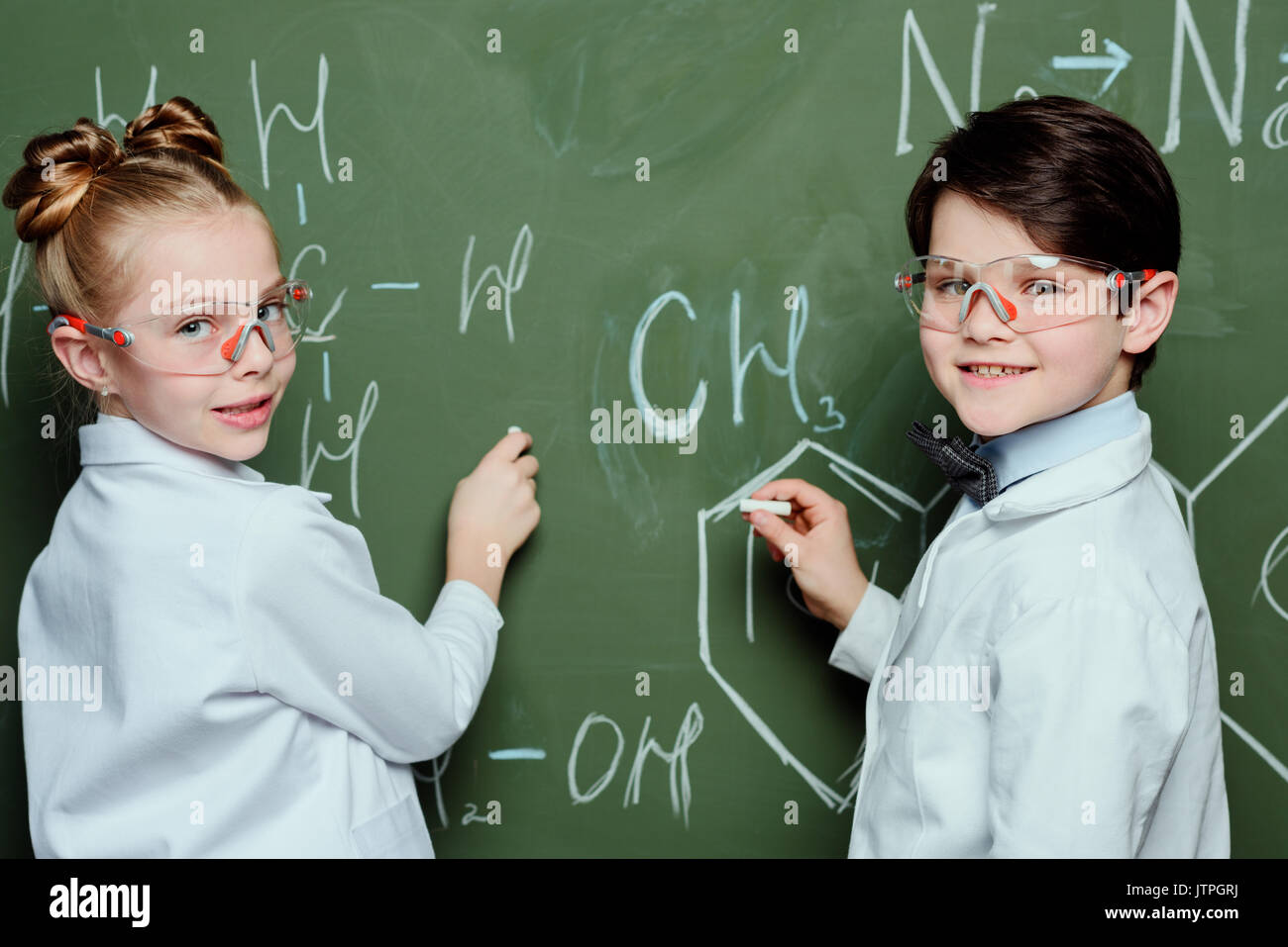 Schoolchildren in white coats and protective eyeglasses drawing chemical formulas on chalkboard and looking at camera, science school concept - Stock Image