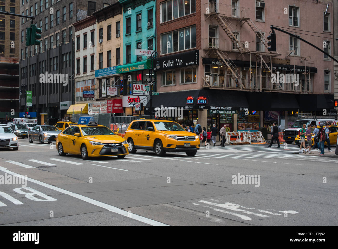 Two yellow cabs lead traffic on 6th Avenue in New York City. Editorial Use Only - Stock Image