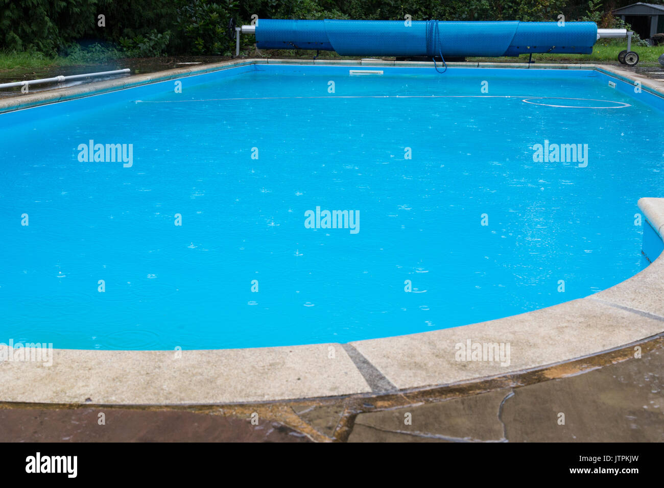 Raindrops Falling into an outdoor swimming pool with blue water - Stock Image