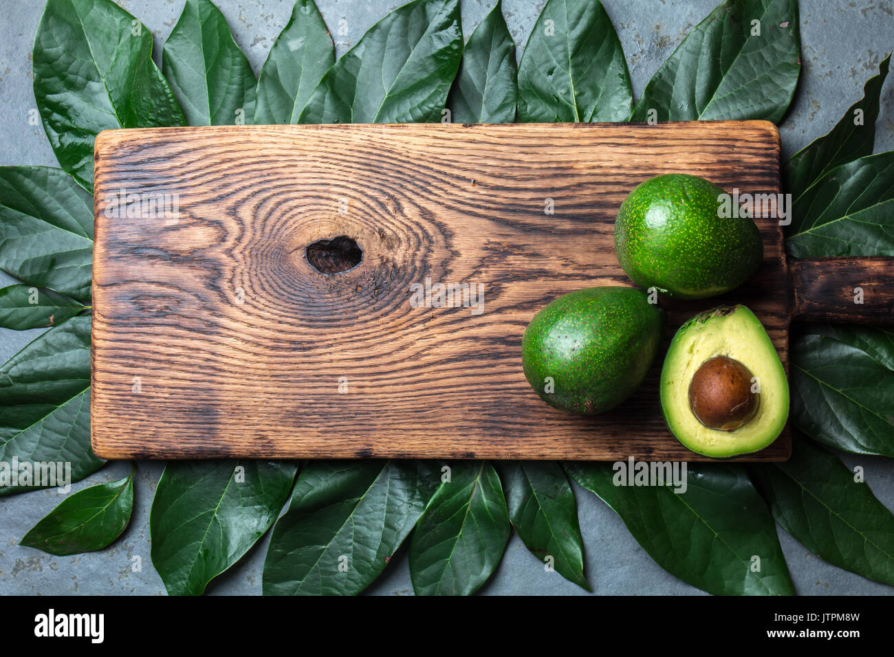 food background with fresh avocado, avocado tree leaves and wooden cutting board. Harvest concept, Guacamole ingredients. - Stock Image
