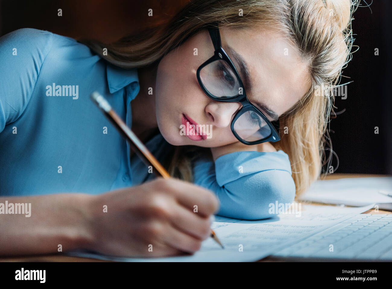 tired blonde caucasian student in eyeglasses lying on hand and writing something with pencil, studying till late - Stock Image