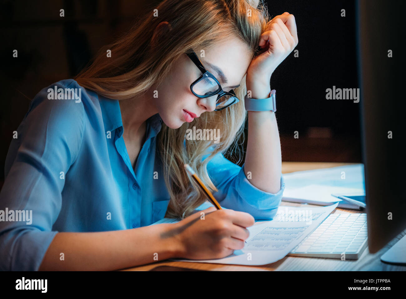 young blonde caucasian businesswoman in eyeglasses writing something with pencil and working till late - Stock Image
